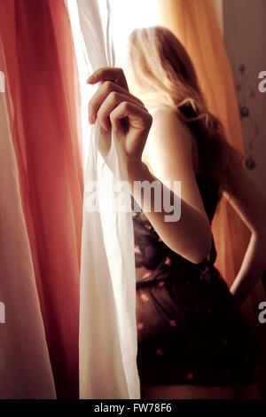 Donna che guarda fuori dalla finestra Immagini Stock