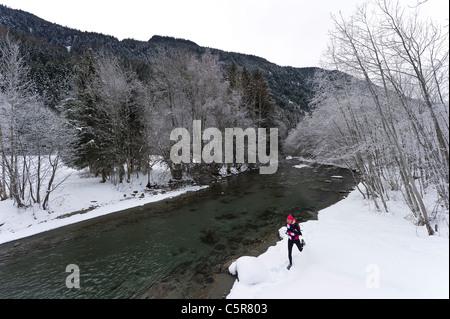 Un pareggiatore che corre lungo un fiume nevoso. Immagini Stock