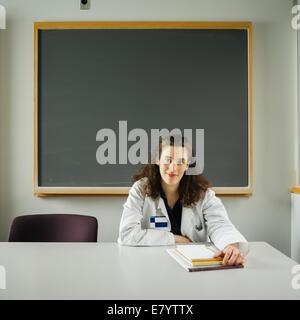Donna al banco in aula con lavagna in background Immagini Stock