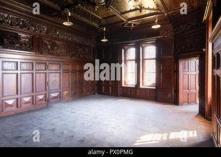 Vista interna della camera con pannelli in legno in un palazzo abbandonato in Polonia. Immagini Stock