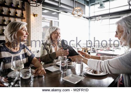 Le donne anziane amici godendo di compleanno pranzo in ristorante Immagini Stock