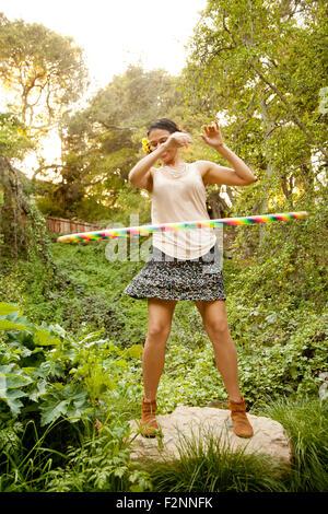Razza mista donna che gioca con il cerchio in plastica Immagini Stock