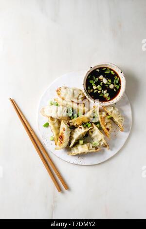 Fritti gnocchi asiatici Gyozas potstickers in bianco piastra ceramica servita con bacchette e una ciotola di soia Salsa di cipolla bianca su sfondo marmo. Appartamento Immagini Stock