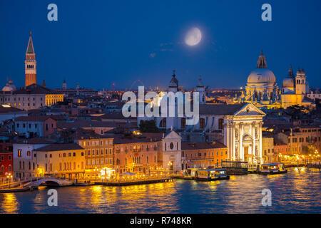 Scenic cityscape con il canale della Giudecca waterfront di notte, Venezia, Veneto, Italia Immagini Stock