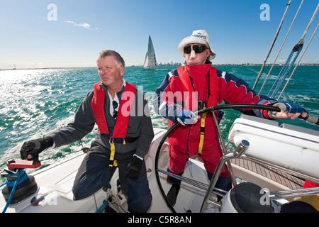 Il capitano dello sterzo è un oceano andando yacht. Immagini Stock