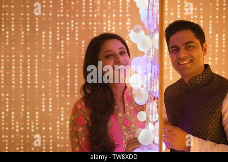 Il marito e la moglie in posa in piedi accanto alle luci Diwali Immagini Stock
