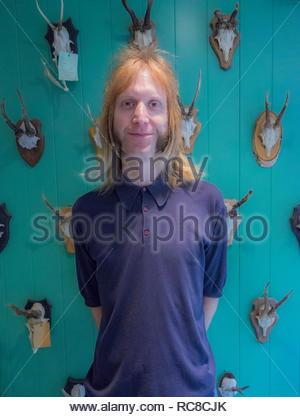 Ritratto di un barbiere contro una parete decorata con teschi di animali Immagini Stock