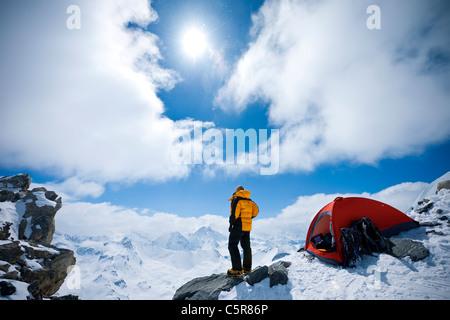 Un alpinista si affaccia su montagne coperte di neve. Immagini Stock