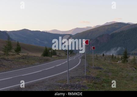 Panorama cinematografico la strada in partenza per le montagne al mattino presto Immagini Stock