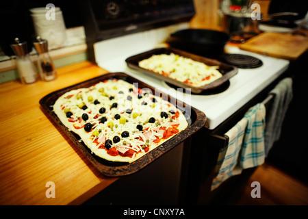 In casa pizza pronta per andare in forno. Immagini Stock