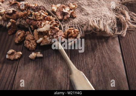 Le noci su un vecchio cucchiaio e composizione dal vecchio legno e materiali Immagini Stock