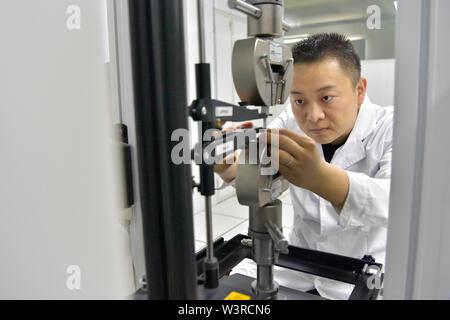"""(190717) -- TURPAN, luglio 17, 2019 (Xinhua) -- Un ricercatore che esegue il test di un pezzo di plastica nel campione a temperatura ed umidità costante camera al Xinjiang Turpan Ambiente Naturale Experimental Research Center di Turpan, a nord-ovest della Cina di Xinjiang Uygur Regione autonoma, 17 luglio 2019. Conosciuta come """"la terra di fuoco"""" con la sua estremamente caldo e il clima è secco, Turpan nel nord ovest della Cina è diventata una delle scelte migliori per il mondo società automobilistica, materiale i fabbricanti e gli istituti di ricerca che cercano un esperimento terreno per condurre prove ad alta temperatura sui veicoli. Attualmente, oltre 30 Immagini Stock"""