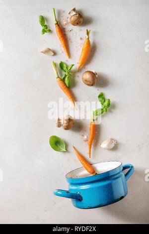 Il basilico fresco erbe con mini carote, sale e funghi champignon levitazione nella coppa blu su bianco Sfondo marmo. Appartamento laico, spazio. La cottura con Immagini Stock