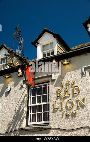 Regno Unito, Cumbria, Hawkshead, Main Street, Pub Red Lion segno con uomo con il maiale e la riproduzione di cornamuse figure sottostanti al piano superiore le finestre dormer Immagini Stock