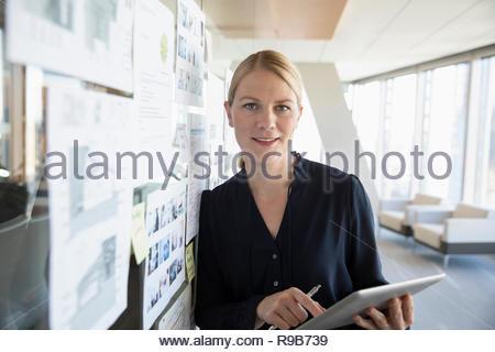 Ritratto fiducioso architetto femmina con tavoletta digitale, rivedendo blueprint in office Immagini Stock