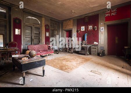 Vista interna di un salotto con mobili antichi e una raccolta di elementi storici in un castello abbandonato in Francia. Immagini Stock