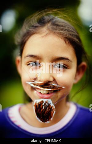 Movember. Ragazza con il suo in casa di baffi e barba che ha bloccato per il suo volto con il nastro adesivo. Immagini Stock