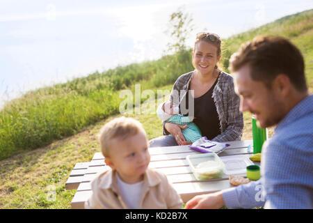 I genitori con figli (18-23, 0-1 mesi) seduti a un tavolo da pic-nic Immagini Stock