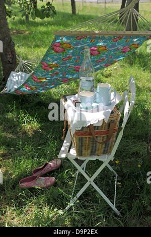 Bottiglia di acqua, cestino da picnic e amaca in giardino Immagini Stock