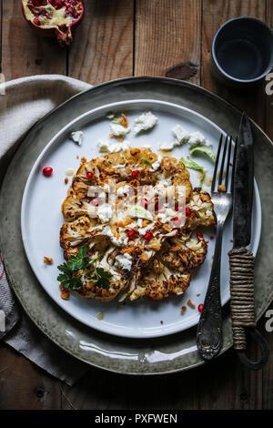 Cavolfiore arrosto di manzo con salsa tahini, il formaggio feta e melograno. Immagini Stock