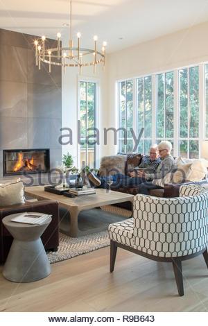 Coppia senior rilassante sul divano, utilizzando tavoletta digitale e bere il vino da camino Immagini Stock