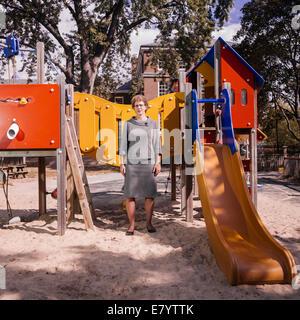 Donna di mezza età in piedi dalla slitta al parco giochi Immagini Stock