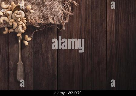 Noci di acagiù su un vecchio cucchiaio e composizione dal vecchio legno e materiale. Vista superiore e spazio vuoto sul lato destro per il testo Immagini Stock