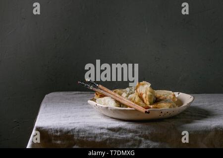 Fritti gnocchi asiatici Gyozas potstickers in bianco piastra ceramica servita con bacchette sulla tabella di lino inumidito. Cena asiatica Immagini Stock