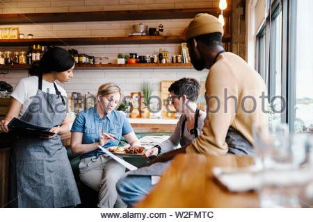 Manager e server incontro in cafe Immagini Stock