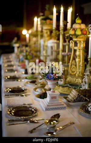 Tavolo da pranzo e candelabri con composizioni floreali e vasellame nella sala da pranzo al Attingham Park, Shrewsbury, Immagini Stock