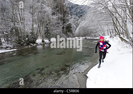 Un pareggiatore che costeggia una nevoso fiume alpino. Immagini Stock