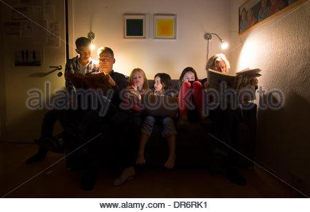 Famiglia seduto in una stanza vivente Immagini Stock