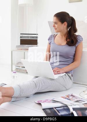 Bruna giovane donna utilizzando portatile a casa Immagini Stock