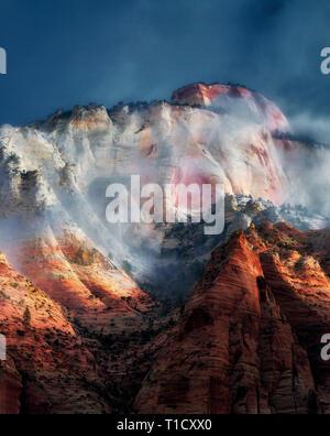 Sun peaking attraverso nuvole temporalesche a est del Tempio. Parco Nazionale di Zion, Utah Immagini Stock
