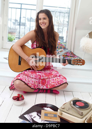 Bruna giovane donna a suonare la chitarra Immagini Stock