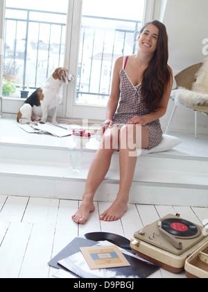 Bruna giovane donna con il cane a casa Immagini Stock