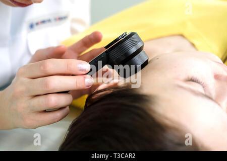 Il dermatologo femmina usando un professionista dermatoscope mentre si esegue un esame della pelle, controllo benigne moli sul viso. Il dermatologo esaminando birthmarks Immagini Stock