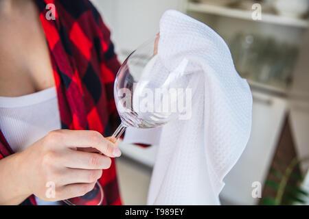 La donna è strofinando il bicchiere di vino con un panno bianco in cucina. Immagini Stock