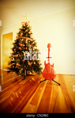 Chrismas avvolto guitar presente e l'albero. Immagini Stock