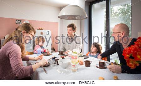 Giovane famiglia avente la colazione con il loro nonno Immagini Stock