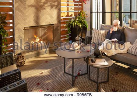 Senior donna rilassante, a bere caffè e la lettura di un libro sul divano accanto al caminetto Immagini Stock
