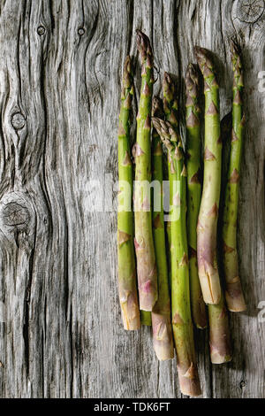 Bundle di materie organiche asparago verde sopra il vecchio sfondo di legno. Laici piana, spazio Immagini Stock