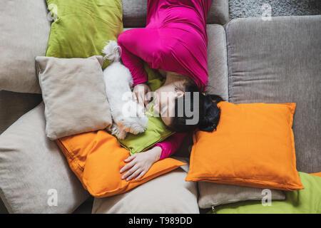 La donna è in stato di stop con il suo cane sul divano con cuscini colorati. Foto scattata da sopra. Immagini Stock