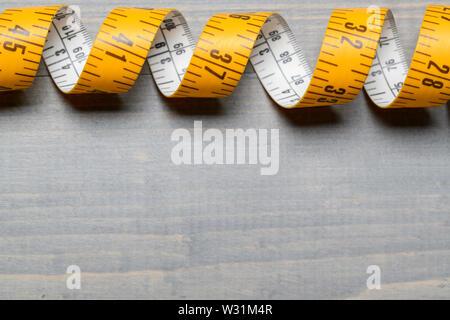 Giallo su misura di nastro di misurazione sul tavolo di legno indietro Immagini Stock