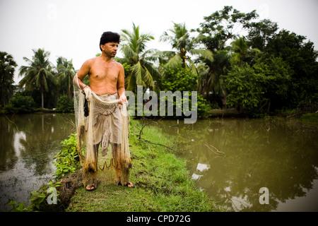 Un pescatore in Bangladesh si prepara a gettò la sua rete da pesca nel laghetto Immagini Stock