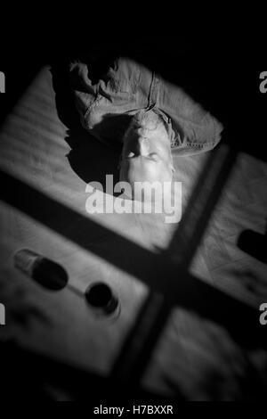 Il vecchio uomo in appoggio sul pavimento. Ritratto in bianco e nero con ombre profonde. Immagine concettuale di Immagini Stock