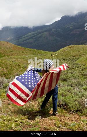 Ragazza con bandiera americana nel campo Immagini Stock