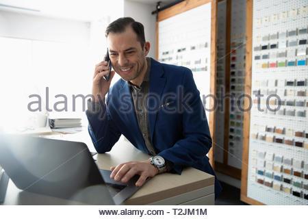 Maschio di interior designer parlando al cellulare al computer portatile in design studio Immagini Stock