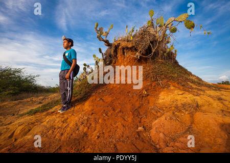 Giovane ragazzo panamense nel paesaggio eroso in Sarigua national park (deserto) nella provincia di Herrera, Repubblica di Panama. Immagini Stock