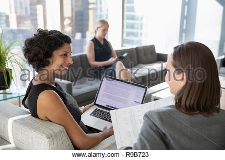 Imprenditrici con il computer portatile e documenti riunione in ufficio Immagini Stock